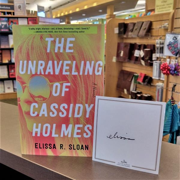 A paperback copy of The Unraveling of Cassidy Holmes by Elissa R Sloan is posed with a signed bookplate