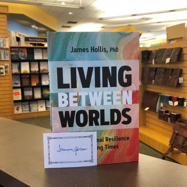 A hardcover copy of Living Between Worlds by Dr James Hollis is posed with a signed bookplate