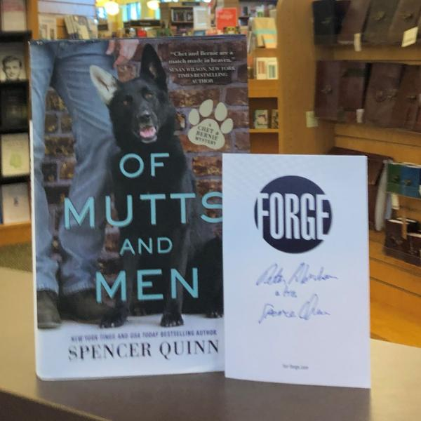A hardcover copy of Of Mutts And Men is posed with a signed Forge Publisher bookplate by Spencer Quinn and Peter Abrams