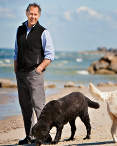 author spencer quinn. smiling, white 71 year old man on a rocky beach with a dog